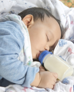 Asian Baby Sleeping And Drinking Milk From The Bottle